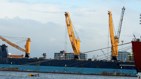 A large bulk carrier loaded with ship cranes. Ship in cargo port terminal. Container ship being unloaded in the Rotterdam harbor. Trade sea port .