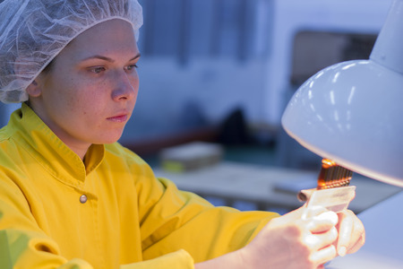 particulates: Female Quality Control Lab Technologist Holding Ampoules