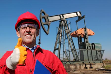 obrero trabajando: Trabajador en trajes rojos y gafas de seguridad que trabajan en una plataforma de perforación. Ingeniero de petróleo y gas. Retrato de un trabajador sonriente.
