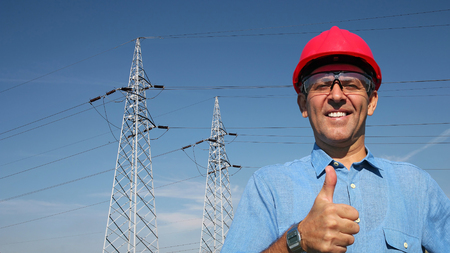 hertz: Thumb up given by smiling engineer. A line of electrical transmission towers carrying high voltage.  Stock Photo