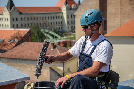 Industrial climbing - Facade Cleaning Service.  Worker preparing for window cleaning on high skyscraper. Stock Photo