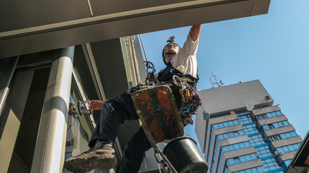 Industrial climbing - Facade Cleaning Service. Workers hanging on climbing ropes.  Stock Photo