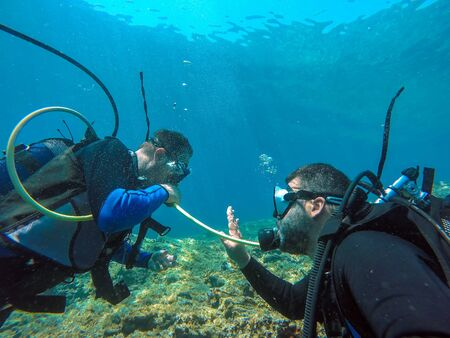A helpful dive buddy shares his air. Scuba diver using hand gestures to communicate with his dive buddy. Stock Photo