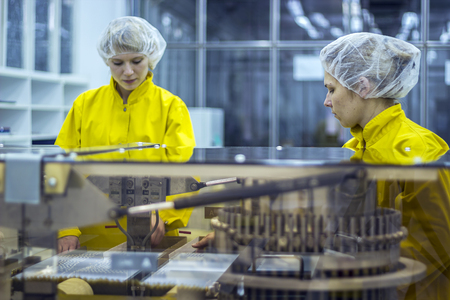 Two Pharmaceutical Factory Workers Wearing Protective Work Wear