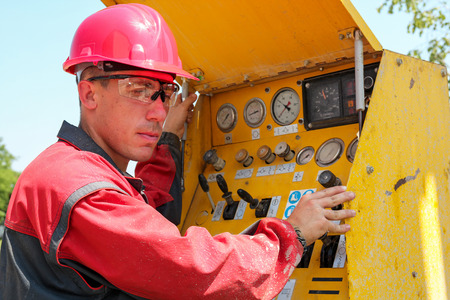 Worker Operating Drilling Rig Control Panel