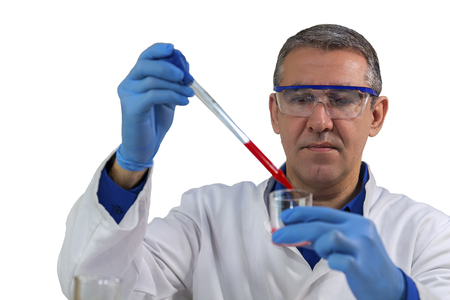 Microbiology Analyst Working with Pipette in Laboratory. Researcher wearing blue protective gloves, white uniform and safety glasses. Pipette dropping red sample into a beaker.