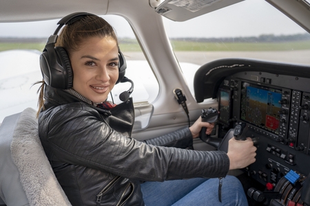 Beautiful Smiling Young Woman Pilot With Headset Sitting in Cabin of Modern Aircraft