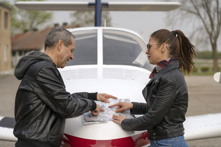 Student and Pilot Discussing Flight Route Over an Aviation Chart Banco de Imagens