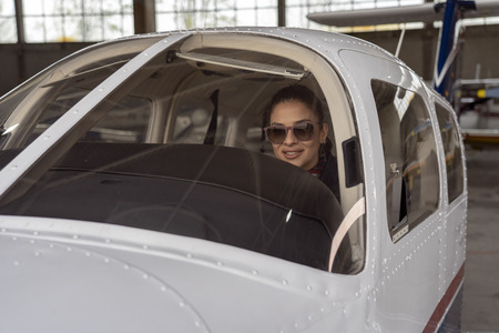 Beautiful Young Woman Pilot Looking Through The Cockpit Window