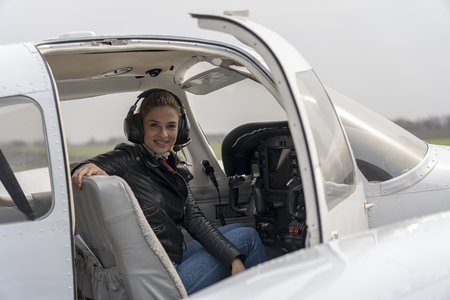 Smiling Young Woman Pilot With Headset Sitting in Cockpit of Private Aircraft Stockfoto