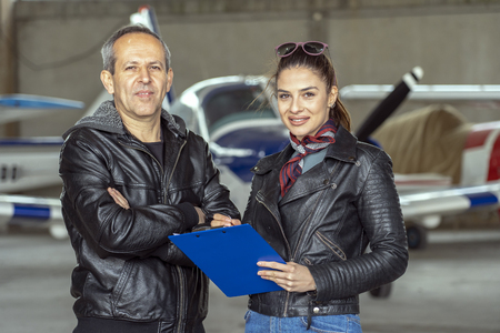 Smiling Woman and Man Pilots in a Hangar Banco de Imagens