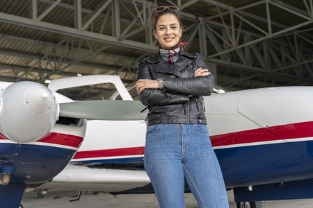 Beautiful Smiling Female Pilot in front of Airplane Фото со стока