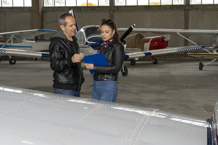 Student Pilot and Flight Instructor Check an Aircraft for Safety in a Hangar