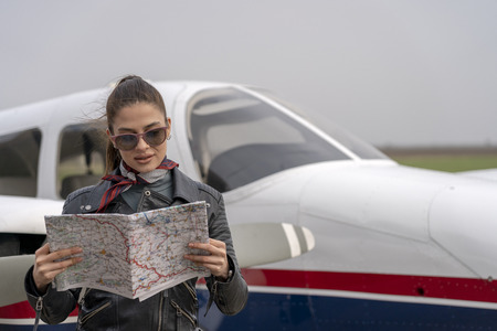 Young Woman Pilot Reading a Map