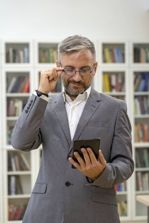 Middle Aged Businessman With Tablet Computer Standing Against Bookshelves