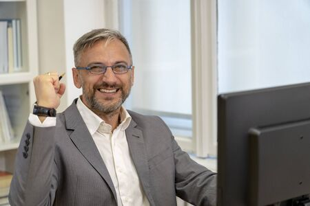 Happy Businessman in Suit Looking at Camera Excited by Good News Stockfoto