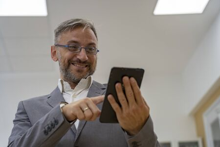 Smiling Middle Aged Businessman With Tablet Computer 版權商用圖片