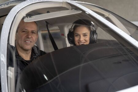 Smiling Female Trainee Pilot and Flight Instructor in an Aircraft Cockpit