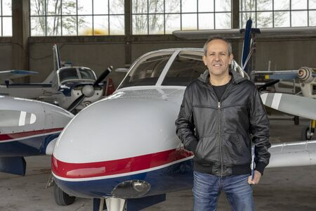Smiling Pilot in front of Small Airplane in a Hangar Imagens