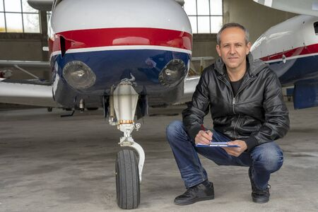 Mature Pilot in front of Small Private Airplane in a Hangar Imagens