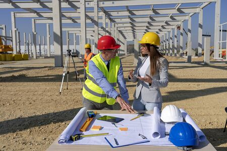Mature Engineer and Female Architect Checking the Construction Blueprint on Constraction Site