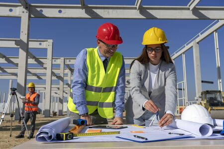 Young Female Architect and Site Supervisor Checking the Construction Blueprint on Construction Site