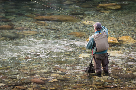 trout fishing: Fisherman on the river Serio while fishing. Typical trout fishing.