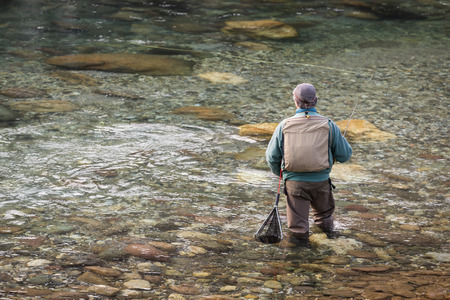 Fisherman on the river Serio while fishing. Typical trout fishing. photo