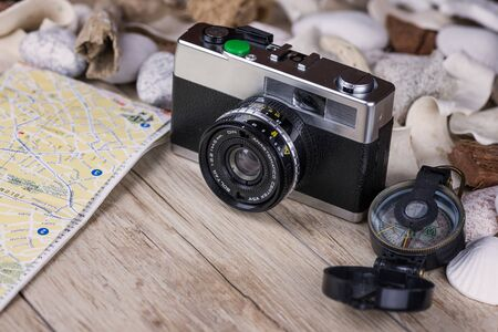 analog camera: In the picture an analog camera film , a compass and a map, on the sides shells and decorative stones .