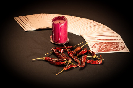cartomancy: In the pictured a deck of cards open fan , a red candle and red pepper dry. Stock Photo