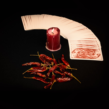 In the pictured a deck of cards open fan , a red candle and red pepper dry. Banco de Imagens