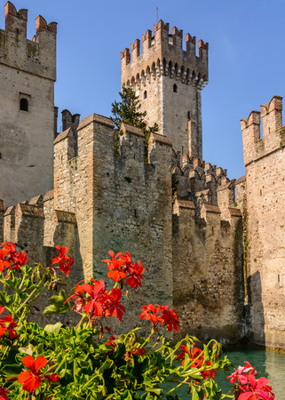 A Scaliger Castle 13th Century with foreground red geraniums.