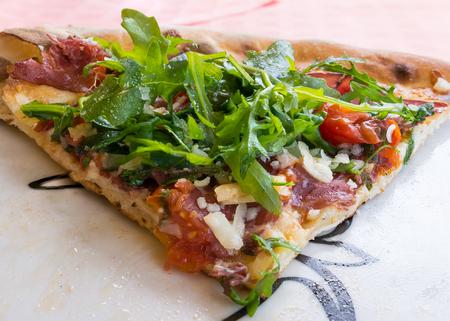 at close quarters: In the picture Italian pizza closeup with Arculacherry tomatotomatomozzarellacheeseparmesan and Bresaola. Stock Photo
