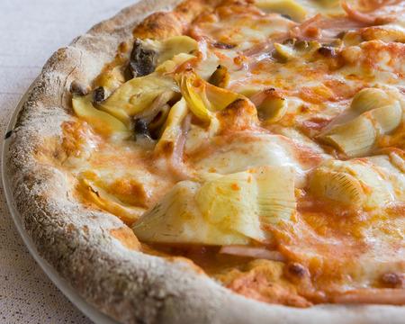 In the picture a  half pizza with tomato, mozzarella, mushrooms, ham and artichokes