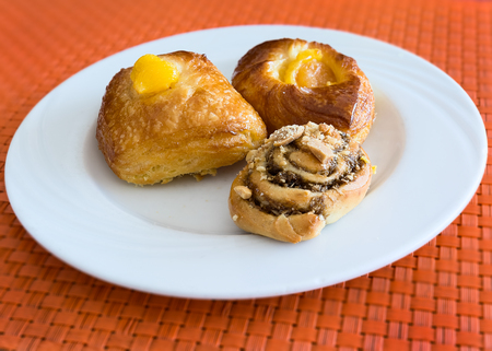 pictured: In the pictured three pastries served on a white plate . Stock Photo
