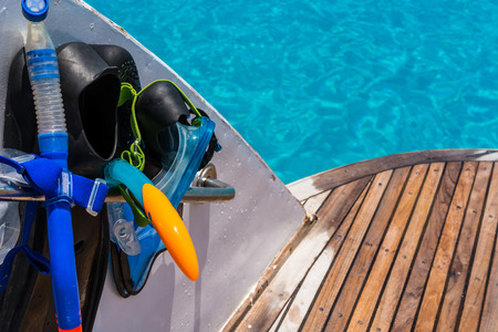 sail fin: In the pictured boat with curved wooden deck wet,on the left  fins,mask,scuba rubber for snorkeling and in the background ocean blue  turquoise.