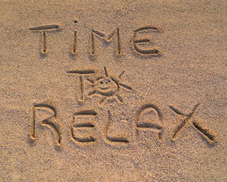 """Op de foto de woorden op het zand """"Tijd om te ontspannen"""""""