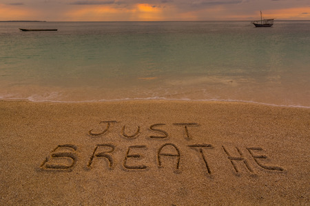 rest and relaxation: In the picture a beach at sunset with the words on the sand Just breathe. Stock Photo