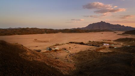 alam: In the picture a beautiful view of a valley in the Egyptian desert at sunset a few kilometers from Marsa Alam, foreground a Bedouin village frequented by many tourists and background the rock mountains.