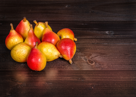 yellow: In the picture a set of pears  Angelica Typical Italian, placed on wooden boards brown and empty space on the right. Stock Photo