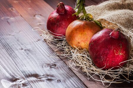 background food: Pictured three pomegranates placed on straw and jute sack on wooden background