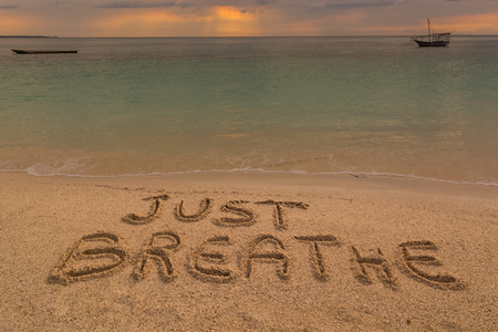 strong message: In the picture a beach at sunset with the words on the sand Just breathe. Stock Photo