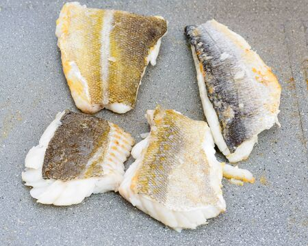 sea bream: Pictured three fillets of sea bream and codfish cooked on the grill outdoor.