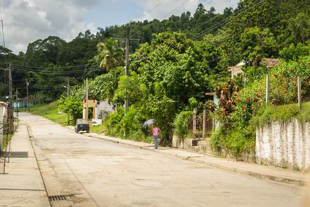 jungla: En la foto de una chica con un paraguas para sombra, caminando en una calle que pasa por el medio de la selva en Cuba Foto de archivo