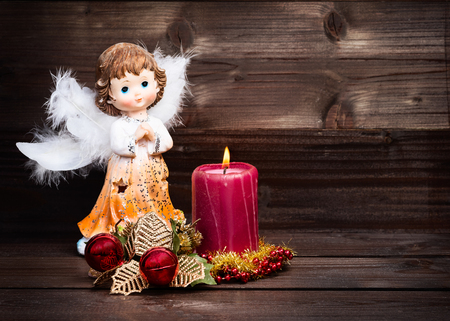 dark angel: Christmas greeting card with candle and angels on wooden background.