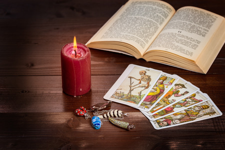color healing: Composition of esoteric objects,candle,Tarots and book used for healing and fortune-telling.