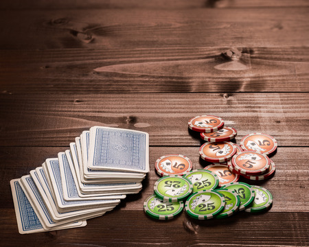 gambling chip: old vintage cards and a gambling chip on a wood table.