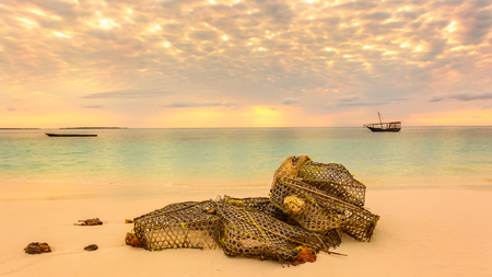 forground: In the beautiful beach of Nungwi Zanzibar in the forground a fishing net on the beach,in background two typical local boats dhows at sunset. Stock Photo