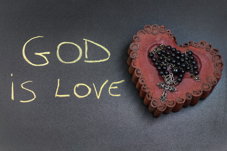 In the picture a rosary iron placed over a heart of red wax, on the left side the inscription God is Love made with a crayon. Imagens