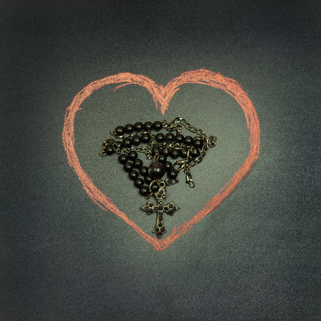 in the picture a rosary iron at the center of a heart drawn with a crayon,square photo. Imagens